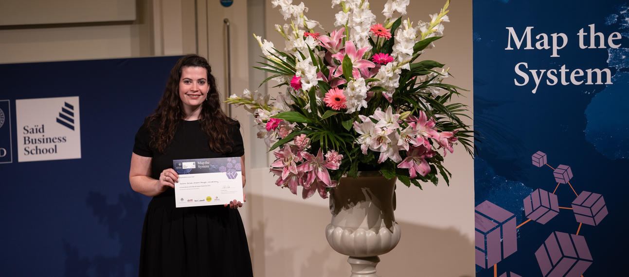 Roisin Dillon, Mount Royal University, holding Map the System 2018 Prize award