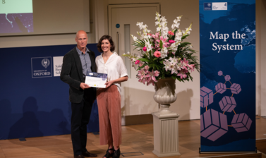 Dr. Abbey Eeles, University of Melbourne holding Map the System 2018 prize award
